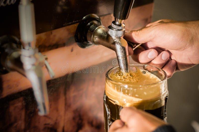 填满用工艺啤酒每品脱玻璃的侍酒者 免版税库存图片