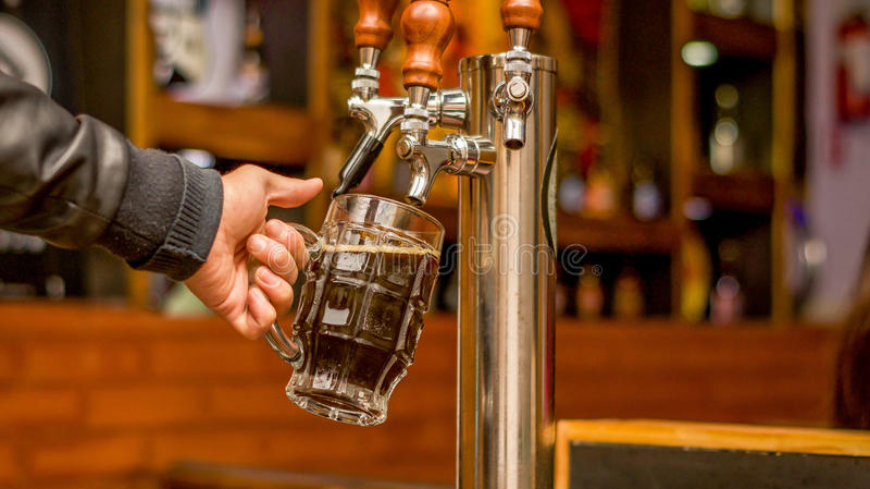 填满用工艺啤酒每品脱玻璃的侍酒者 免版税库存照片