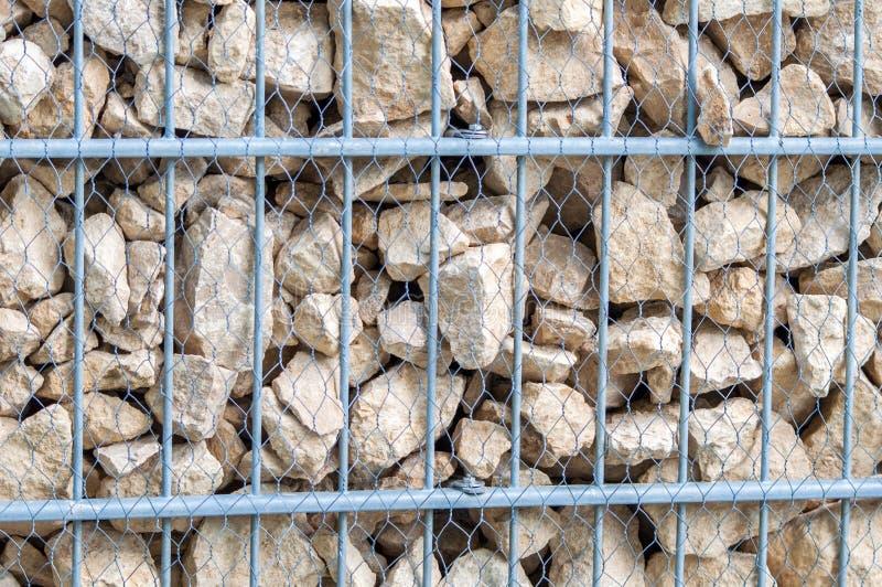 墙壁由岩石做成,动物园操刀与网的和金属条板箱 免版税库存照片