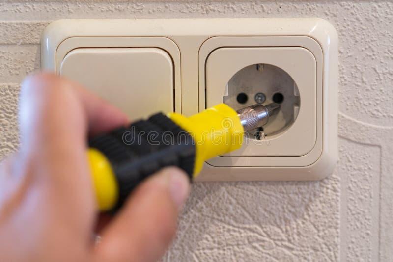 墙壁电源插座设施 人修理一个电子出口,在墙壁的插口的电工的手特写镜头  ?? 免版税库存图片