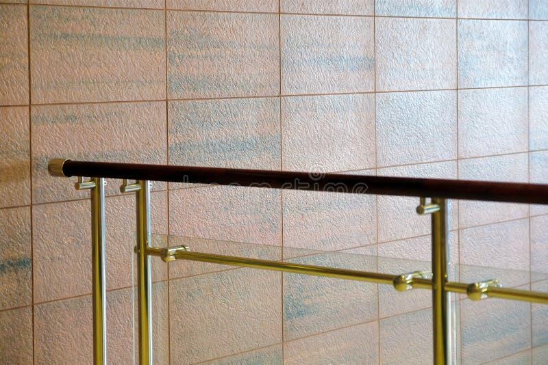 墙壁结构由在花岗岩下的石块做成 自然石纹理 布朗红色石头 金属栏杆与 库存照片