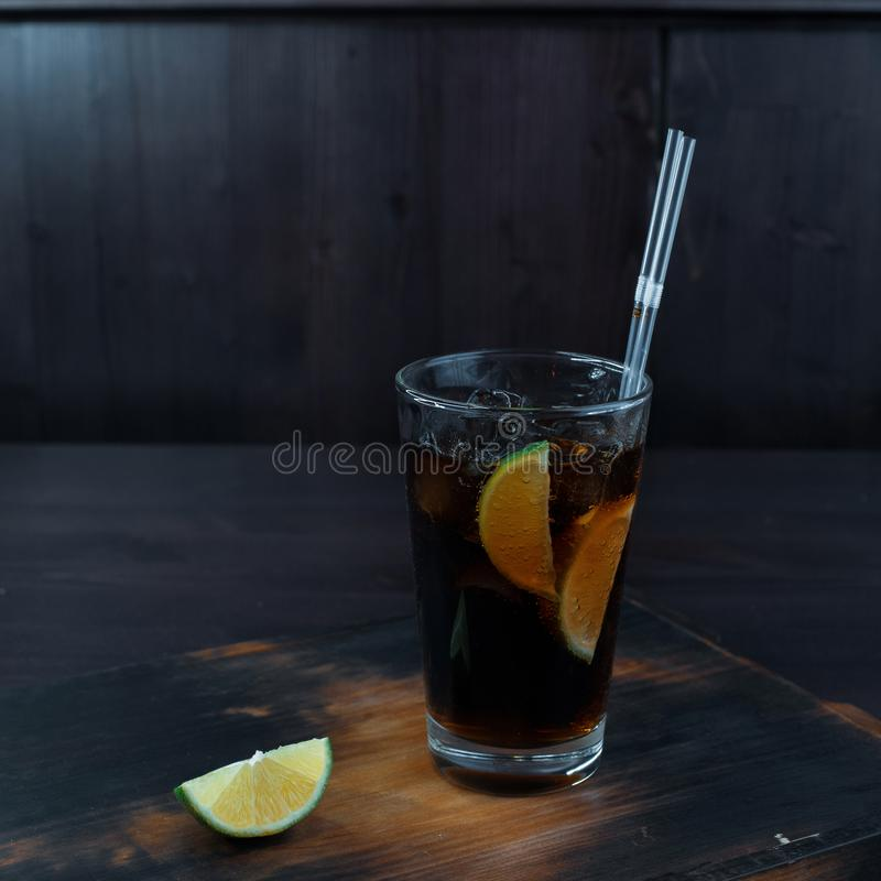增加冰、威士忌酒和可口可乐,石灰切片的原始的可口鸡尾酒在一张木桌上站立 免版税库存图片