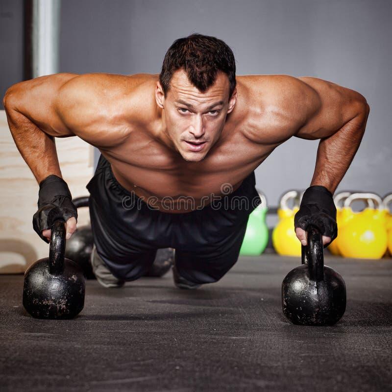 增加在做健身训练的kettlebells人 库存照片
