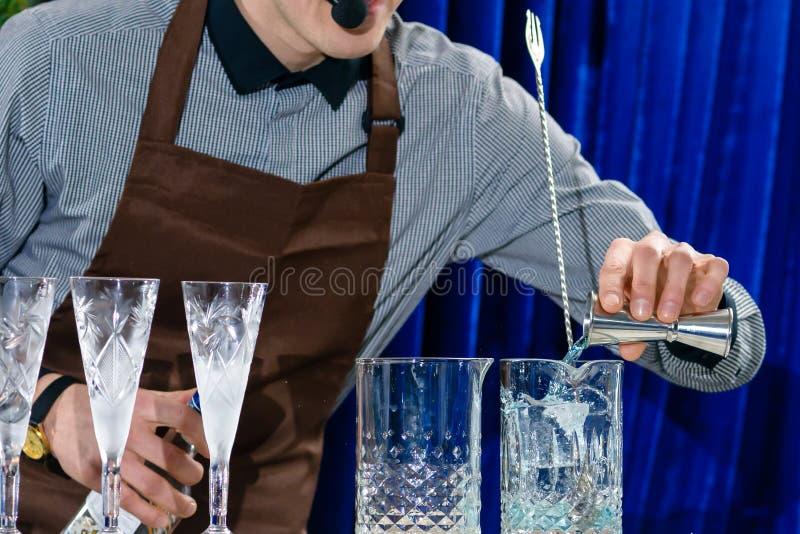 增加在玻璃的未认出的男服务员液体在酒吧柜台 库存照片