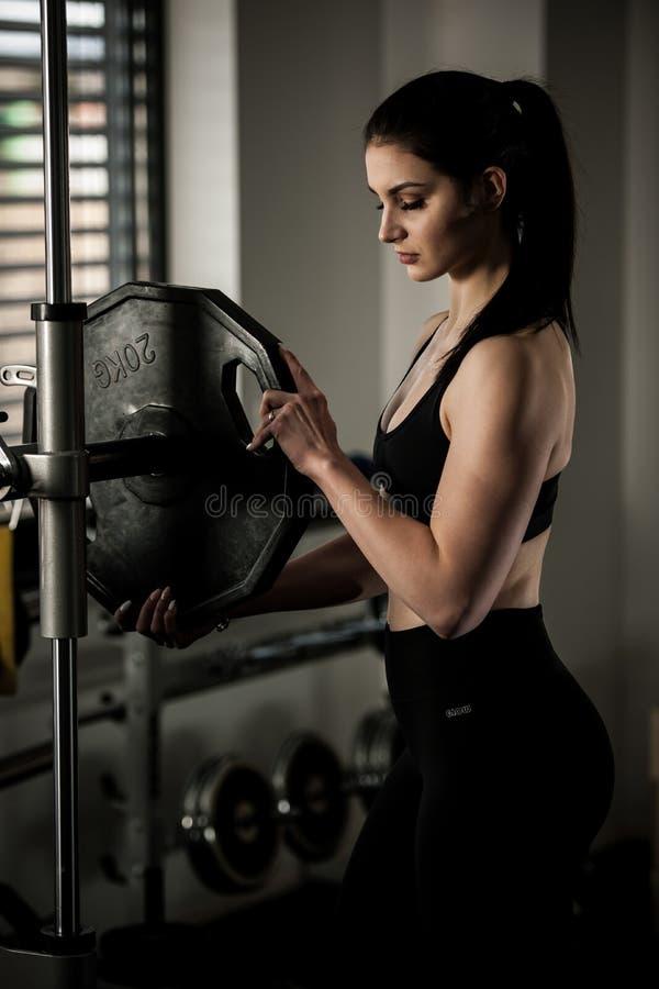 增加在酒吧的妇女重量作为她在健身健身房的锻炼 免版税库存照片