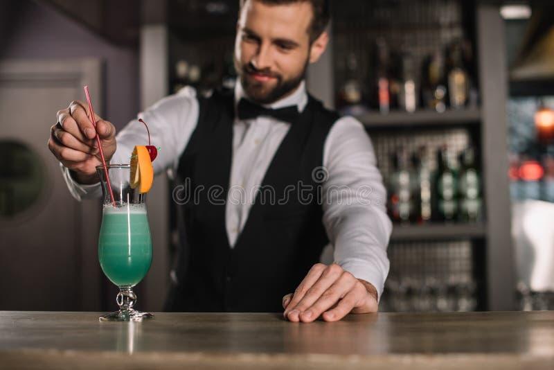 增加塑料秸杆的微笑的侍酒者 免版税库存图片