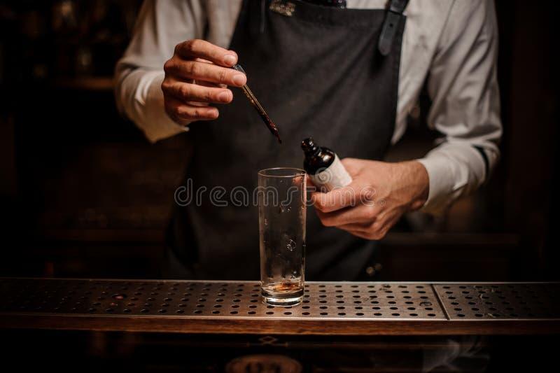 增加棕色苦涩的男服务员入鸡尾酒杯 免版税库存照片