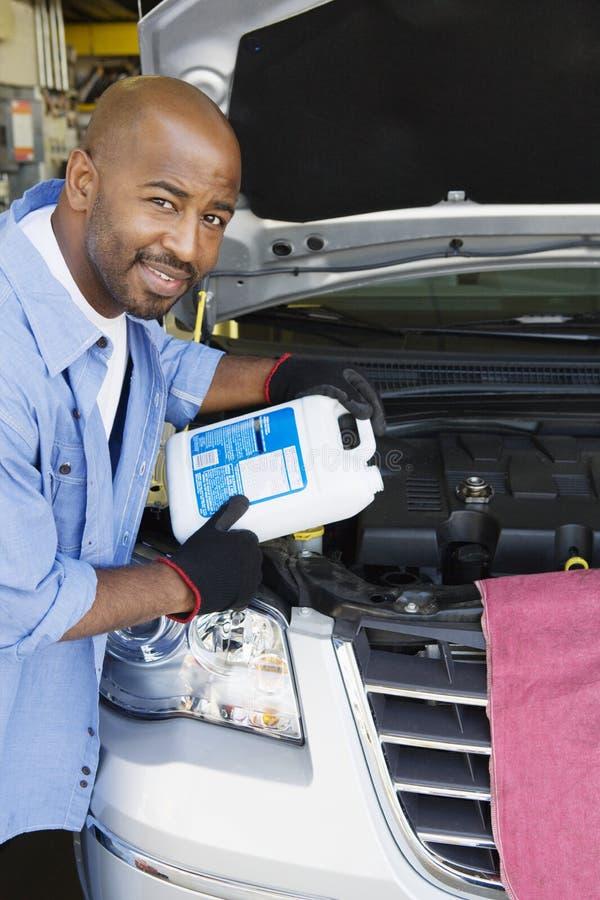 增加流体的汽车机械师到微型货车 免版税库存照片