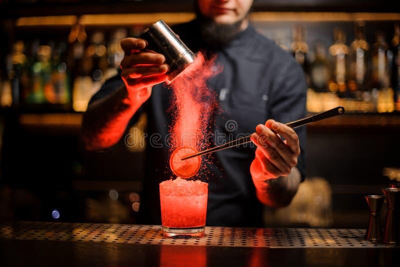 增加香料粉末的男服务员入与切片的一个鸡尾酒杯  免版税库存图片