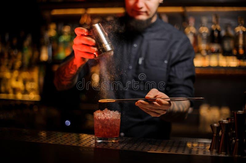 增加香料粉末的男服务员入鸡尾酒杯 库存图片