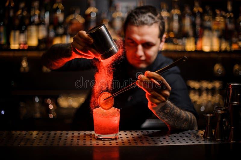 增加香料粉末的被刺字的男服务员入一个鸡尾酒杯与 库存图片