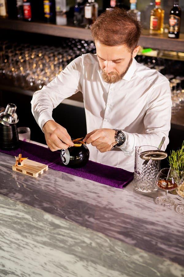 增加鸡尾酒成份的男服务员 免版税库存图片