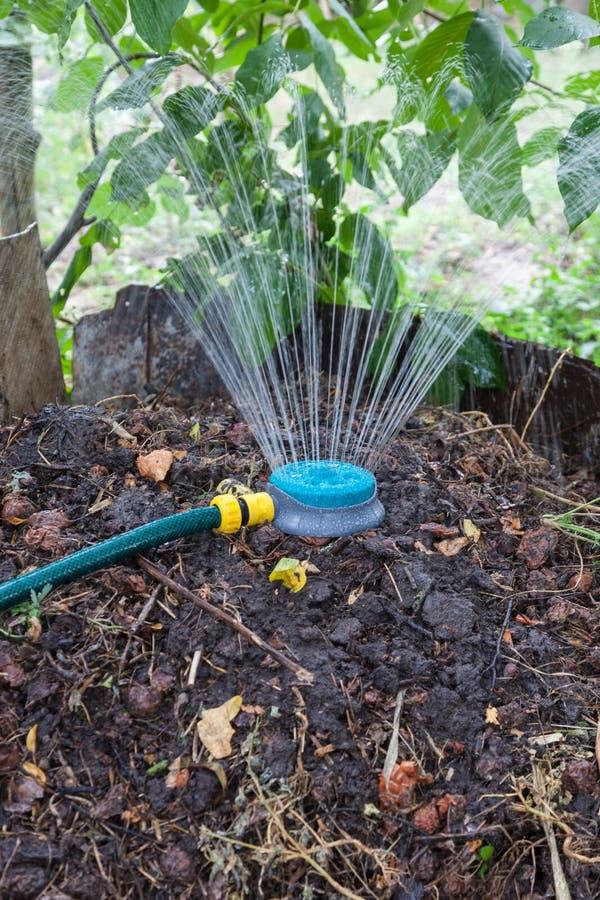 增湿使用喷水隆头的天然肥料堆 免版税图库摄影