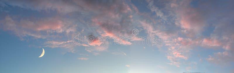 增长的月亮或月牙在天蓝色的天空与桃红色云彩在日落-和谐本质上 库存照片