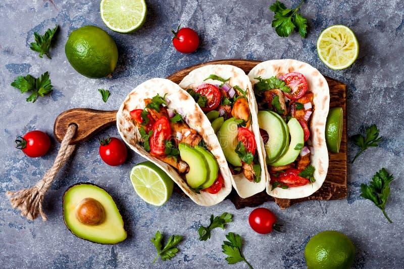 墨西哥人烤了鸡炸玉米饼用鲕梨,蕃茄,在土气石桌上的葱 Cinco de马约角党的食谱 库存图片