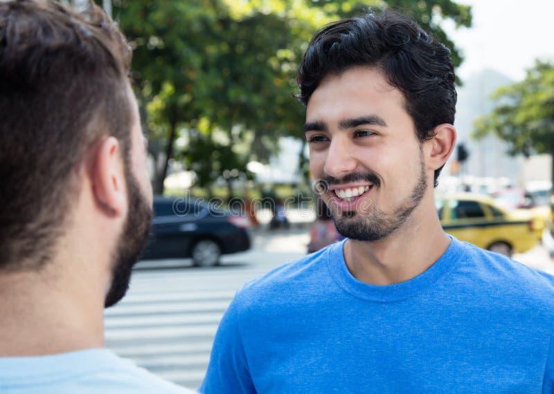 墨西哥人谈话与白种人朋友 免版税库存图片