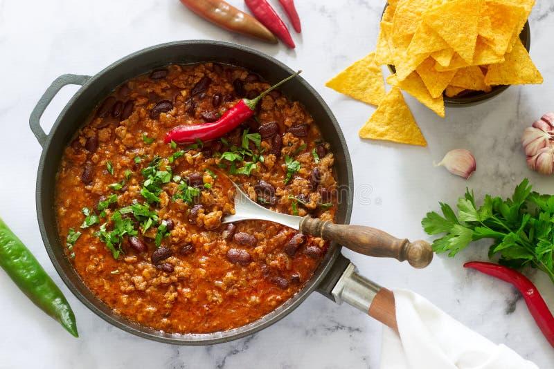 墨西哥和美国食物辣豆汤服务与烤干酪辣味玉米片、胡椒和草本 免版税库存照片