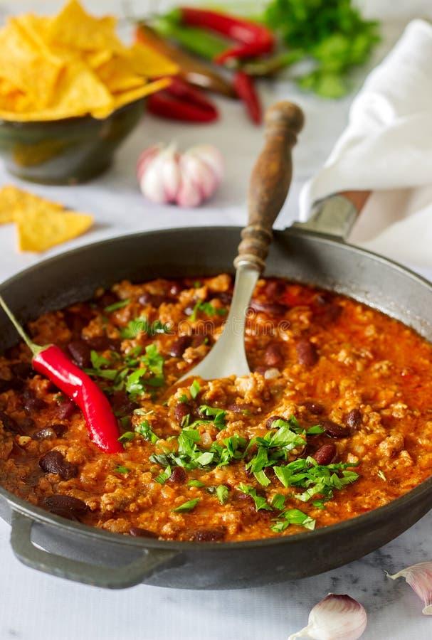 墨西哥和美国食物辣豆汤服务与烤干酪辣味玉米片、胡椒和草本 图库摄影