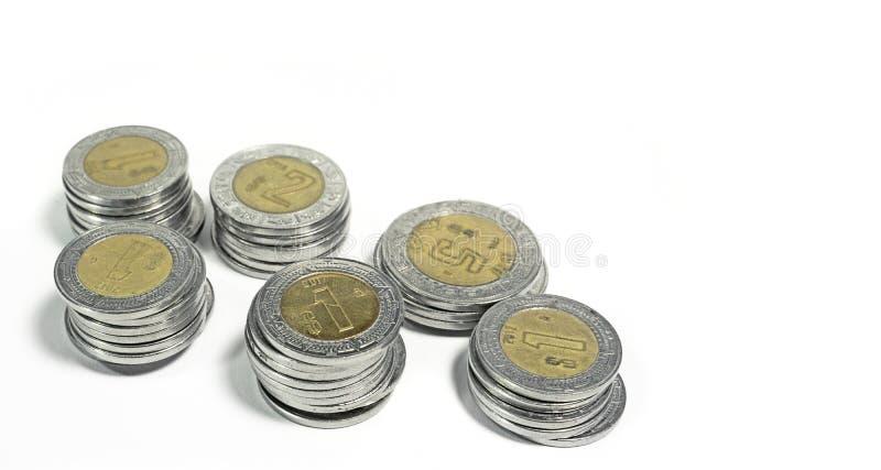 墨西哥比索,各种各样的衡量单位被堆积的硬币在白色背景的 免版税库存照片