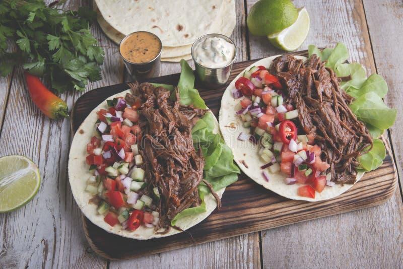 墨西哥炸玉米饼用烤牛肉、调味汁和辣调味汁蕃茄 免版税库存照片