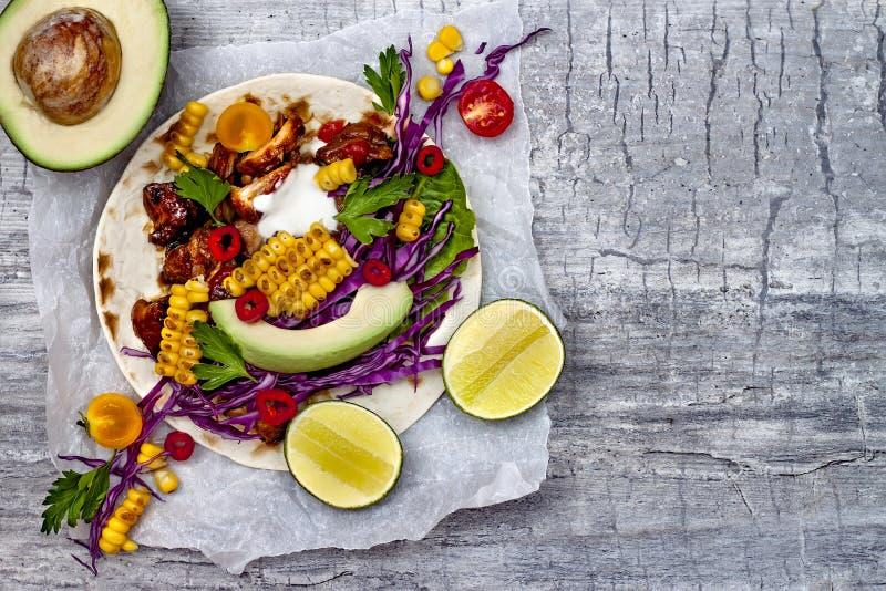 墨西哥炸玉米饼用鲕梨、慢熟肉、烤玉米、红叶卷心菜slaw和辣椒辣调味汁在土气石桌上 库存图片