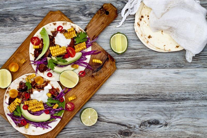 墨西哥炸玉米饼用鲕梨、慢熟肉、烤玉米、红叶卷心菜slaw和辣椒辣调味汁在土气石桌上 免版税库存图片