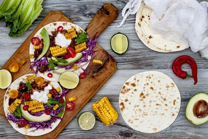 墨西哥炸玉米饼用鲕梨、慢熟肉、烤玉米、红叶卷心菜slaw和辣椒辣调味汁在土气石桌上 免版税库存照片