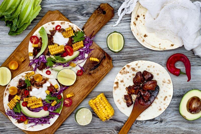 墨西哥炸玉米饼用鲕梨、慢熟肉、烤玉米、红叶卷心菜slaw和辣椒辣调味汁在土气石桌上 库存照片