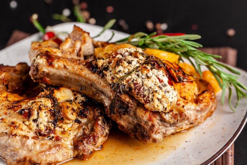 墨西哥烹调的概念 烤猪肉牛排用辣调味汁、红辣椒辣调味汁、桃子和虾 库存照片