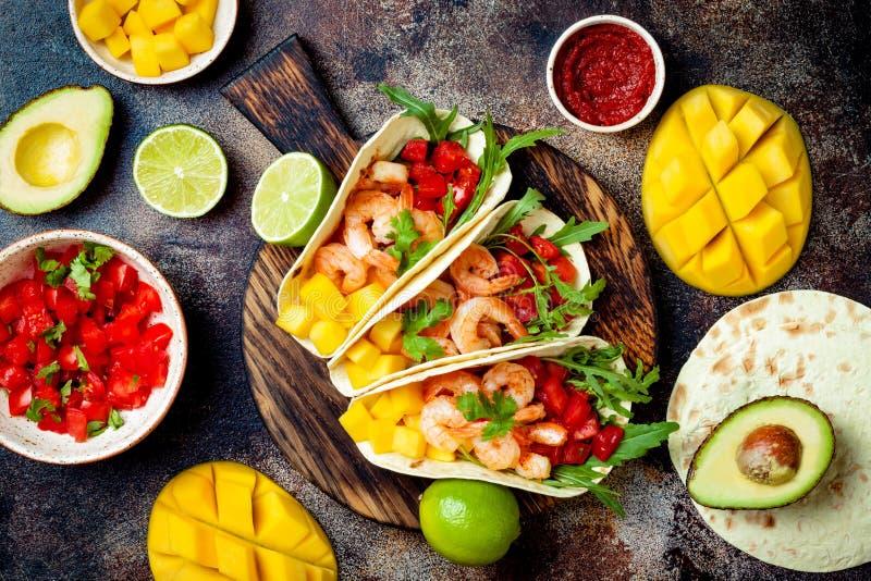 墨西哥虾炸玉米饼用鲕梨,蕃茄,在土气石桌上的芒果辣调味汁 Cinco de马约角党的食谱 图库摄影