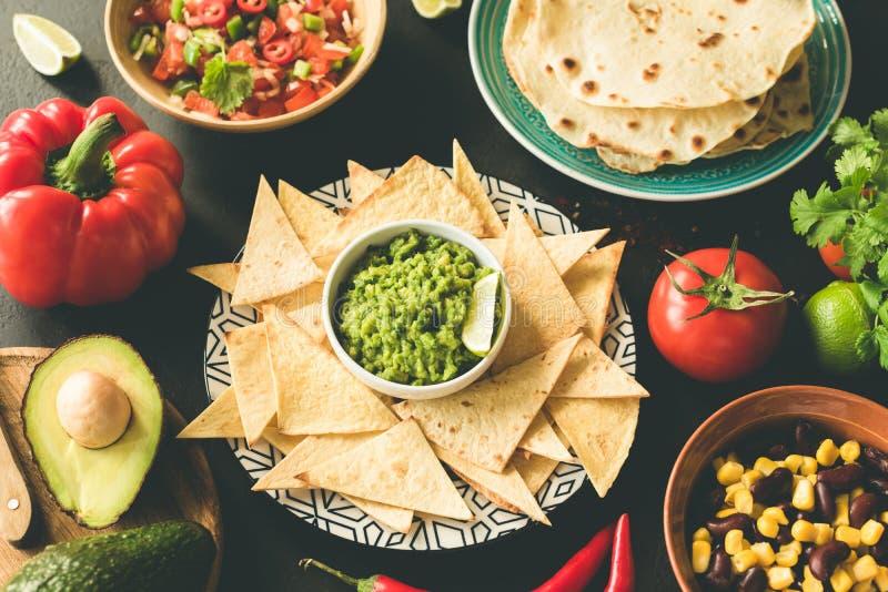 墨西哥食物选择鳄梨调味酱捣碎的鳄梨酱辣调味汁烤干酪辣味玉米片豆 库存照片