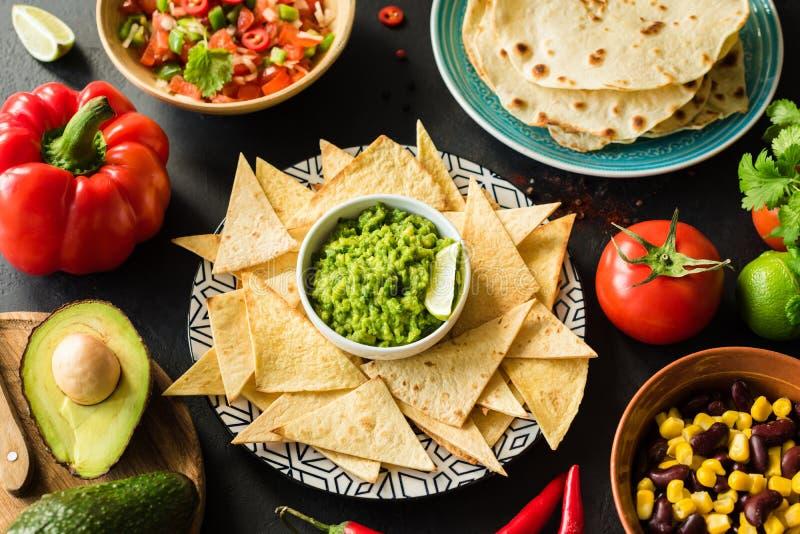 墨西哥食物鳄梨调味酱捣碎的鳄梨酱烤干酪辣味玉米片玉米片辣调味汁和豆 免版税库存图片