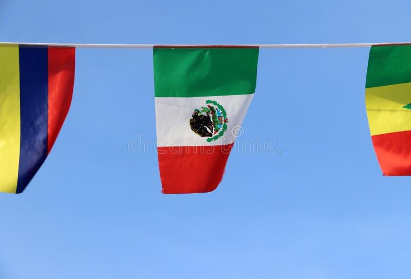 墨西哥,它的微型织品路轨旗子是垂直三色绿色,白色和与国民的红色徽章 免版税库存图片