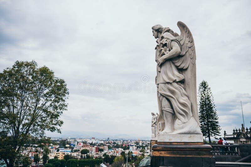 墨西哥- 9月20 :守护天使雕象Tepeyac小山和都市风景位于背景 免版税库存图片