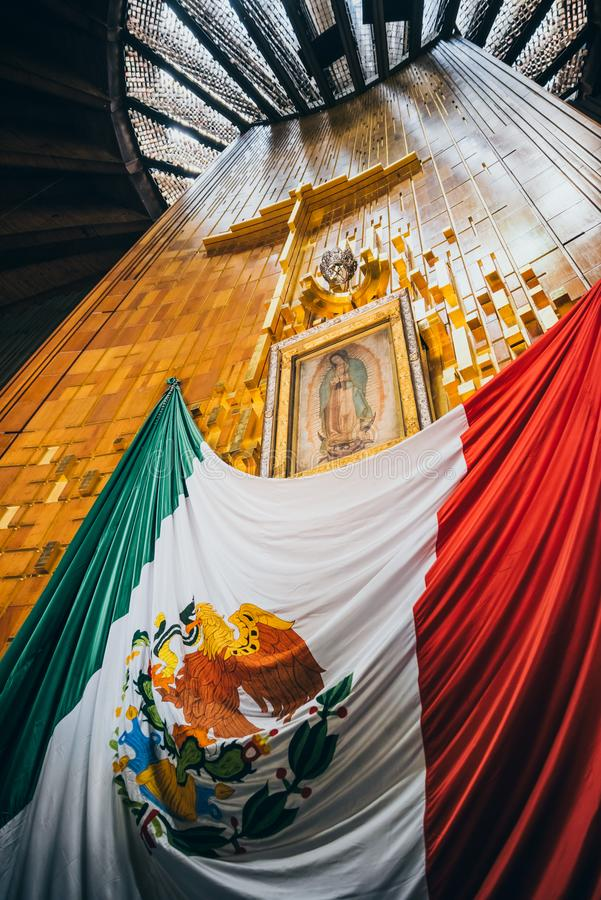 墨西哥- 9月20 :横渡,瓜达卢佩河贞女的图象和墨西哥国旗在我们的夫人瓜达卢佩河大教堂  库存照片