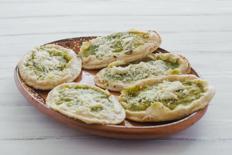 墨西哥sopes用搓碎干酪和绿色辣调味汁,墨西哥食物辣在墨西哥 免版税库存照片