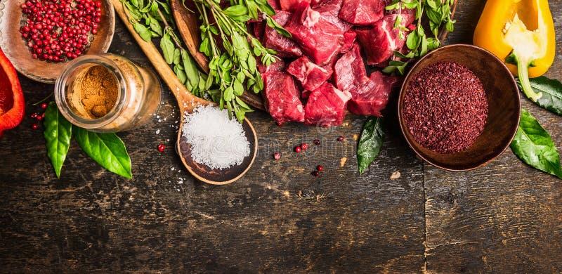 墩牛肉或炖煮的食物烹调的成份:生肉、草本、香料、盐菜和匙子在土气木背景,顶视图的 免版税图库摄影