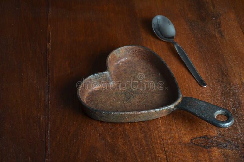 壁炉边塑造了有银色茶匙子的生铁平底深锅在木头 免版税图库摄影