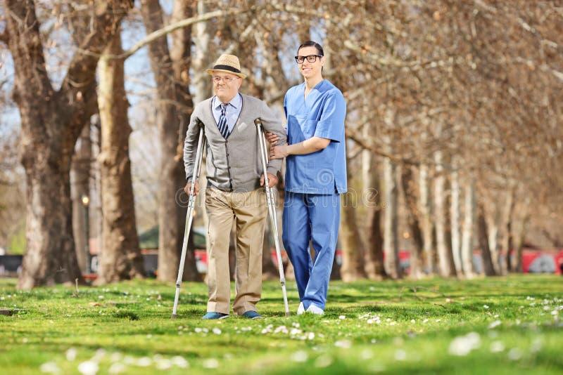 绅士和走在公园的一位男性护士 免版税库存图片