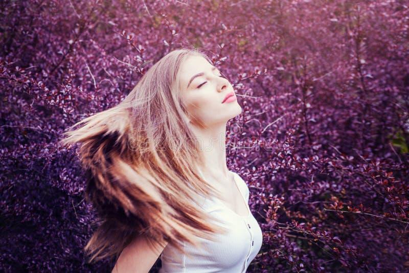 壮观的妇女画象有吹的头发的在开花紫色花背景 免版税库存照片