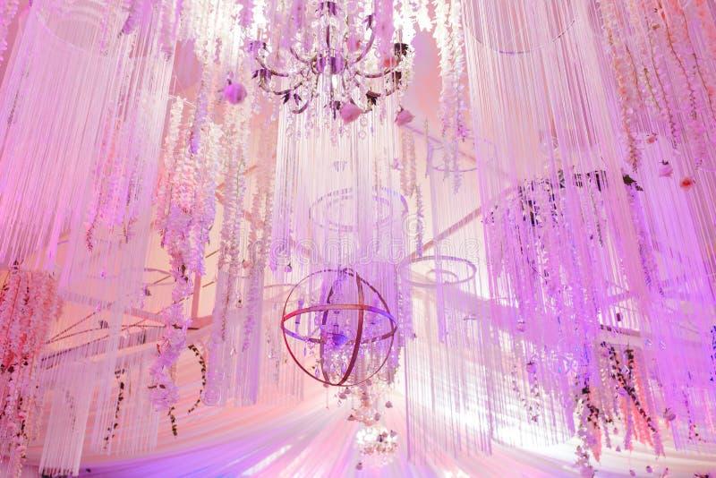 壮观的枝形吊灯从白色天花板粉色垂悬 餐馆的婚姻的装饰 库存图片