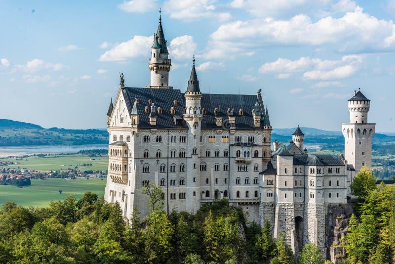 壮观的童话城堡新天鹅堡,巴伐利亚阿尔卑斯山脉的主要旅游景点在一个美好的夏天 免版税库存图片