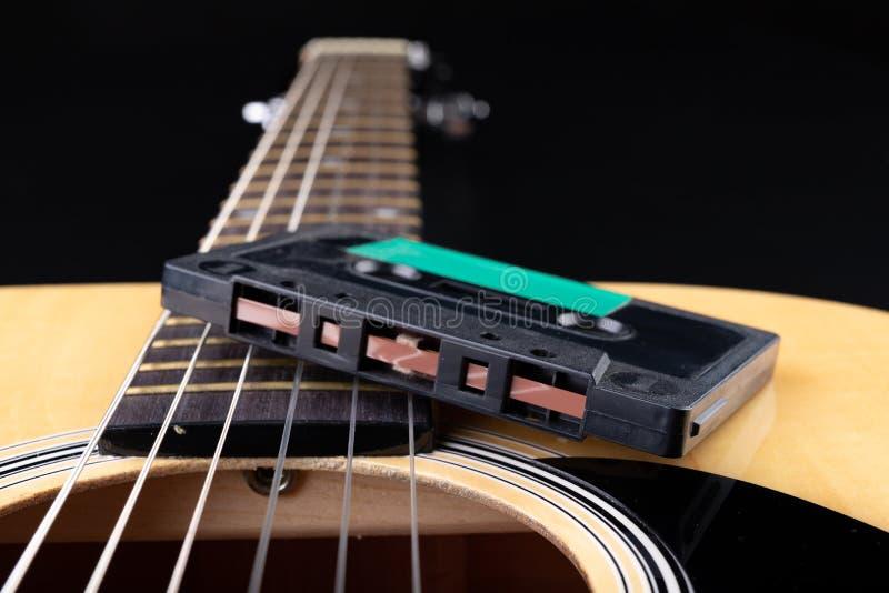 声学吉他和盒式磁带 乐器和老音乐载体 免版税库存照片