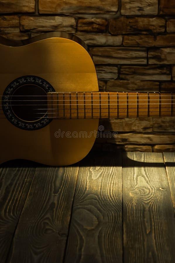声学吉他在砖墙的背景说谎 库存图片