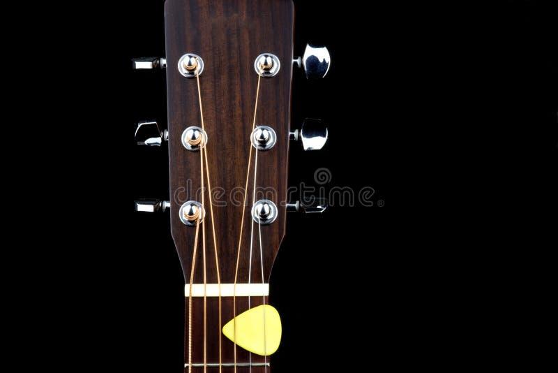 声学吉他有琴拨的钉头在黑背景 图库摄影