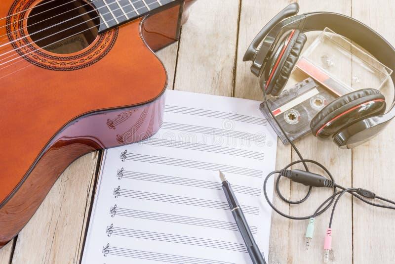 声学吉他,活页乐谱,大耳机,钢笔,磁带c 免版税图库摄影