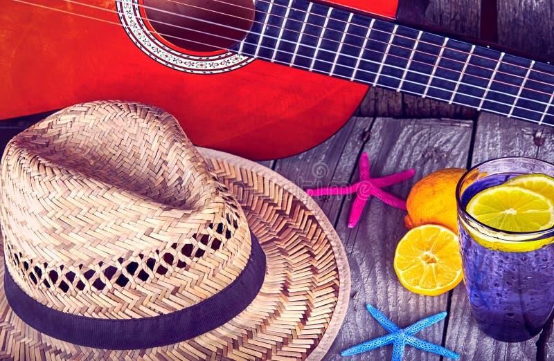 声学吉他帽子海星和杯鲜美新鲜的柠檬水用在葡萄酒木头的柠檬 免版税库存图片