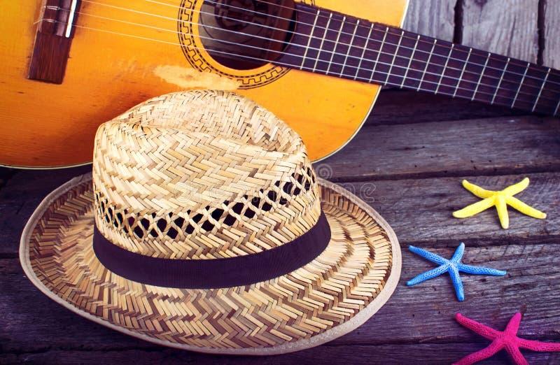 声学吉他星帽子和海星在难看的东西木头背景 库存照片