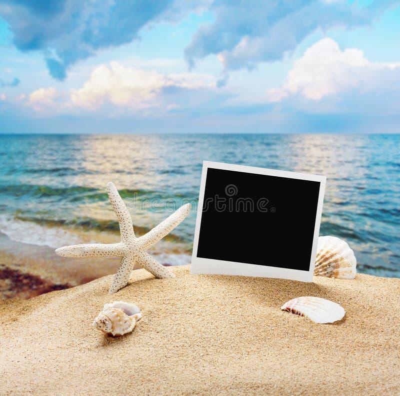 贝壳和老照片框架在沙子 免版税库存图片
