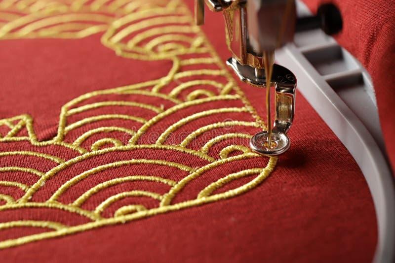 壳样式构筑的猪概述刺绣与金子的在现代刺绣机器-春节概念的红色织品 库存照片